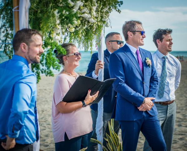 Groom Groomsmen and celebrant watching bride Celebrant Direct